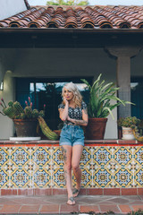 Summer Fashion - Blond Woman in Front of Spanish Building with Cactus Plants