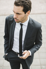 Young businessman typing with a phone