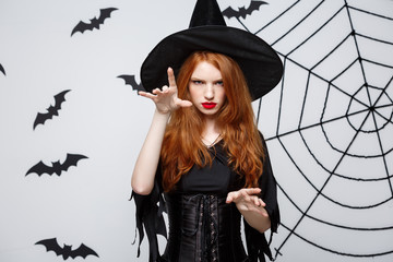 Halloween witch concept - Halloween Witch casting spells with serious expression over dark grey studio background with bat and spider web.
