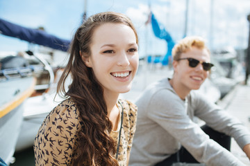 A beautiful girl sitting at the dock with a friend happily smiling