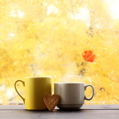 hot autumn love/ two mugs with cookies in the shape heart on background  window after rain
