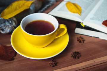 Yellow cup of tea with books and autumn leaves