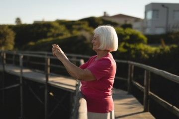 Senior woman clicking pictures on the bridge