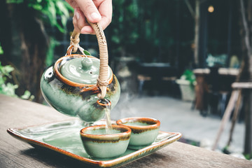 Hand pouring hot tea in the morning with fresh and happy, vintage tone