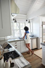Rear view of woman working in modern kitchen at home