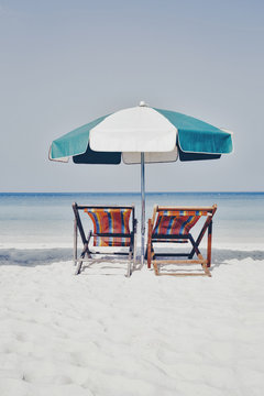 White sandy beach with sun chairs and umbrella