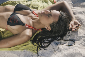 Young Sexy Hispanic-American Woman Wearing Bikini Sunbathing in Miami Beach in Summer