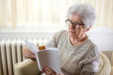 Senior woman reading book at home.