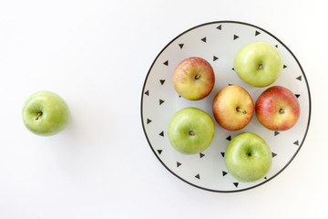 Top view of Red and green apples in white plate with black triangles pattern and green apple on white background.