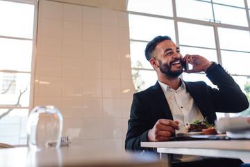 Businessman at restaurant making a phone call