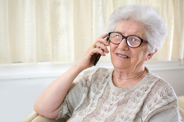 Old woman talking on the telephone at home.