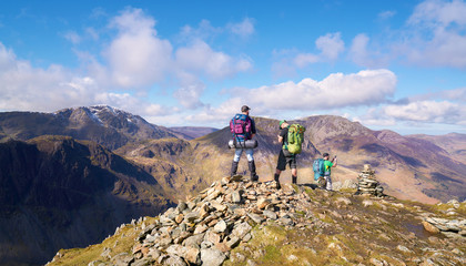 Three hikers looking out over the summits of High Crag, High Stile and Pillar from the summit of Fleetwith Pike, English Lake District.
