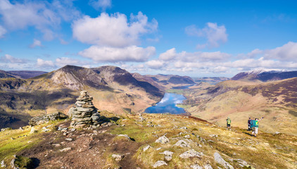 Three hikers descending the summit of Fleetwith Pike, English Lake District with views of High Crag, High Stile and Red Pike