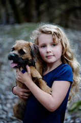 Young girl holding her Border Terrier