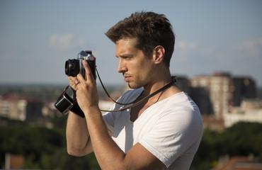 handsome man with retro camera outdoor