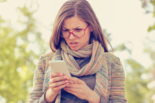 Young woman looking angry at the phone