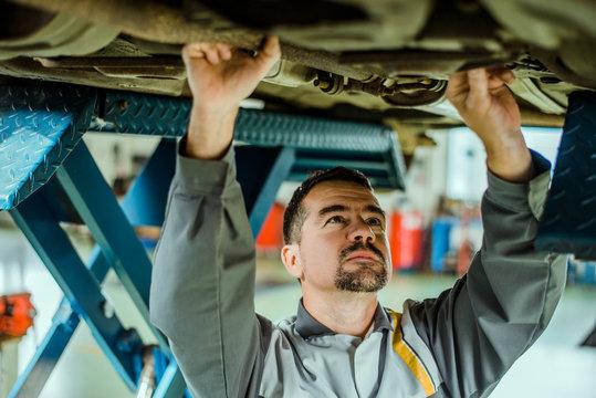 Professional mechanic reparing a car.