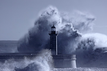 Lighthouse in the middle of stormy waves Wall mural