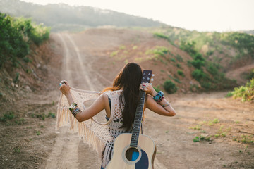 Hippie Woman Carrying her Guitar in the Mountains