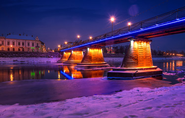 bridge through the river Uzh at night. beautiful cityscape of old european town Uzhgorod in winter