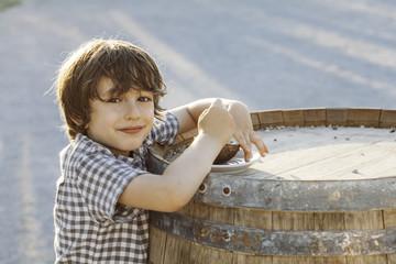 Cute boy eating at a big barrel table