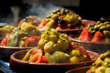A lot of warm tagines with delicious vegetables on a market