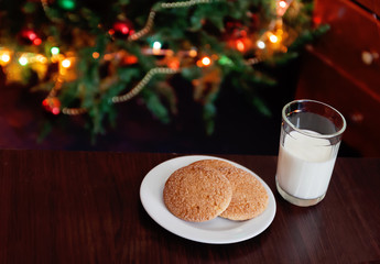 Christmas cookies and milk with note for Santa in front of lights of new year tree