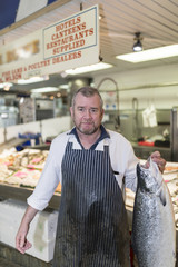 Male fishmonger wearing an apron holding large and whole salmon fish in front of display counter early in the morning on a market in England, UK.