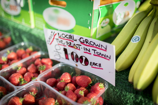 Close up of a hand written sign on an English market stall stating Locally Grown, the best in town, only £1,00 for strawberries