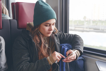 Modern people city lifestyle. Young urban woman using phone app and wireless headphones to listen to music or play video games online.