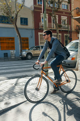 Young man with a city bike waiting to cross the street