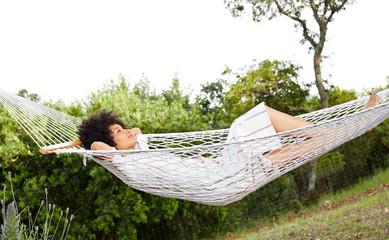 African American woman relaxing in hammock in backyard