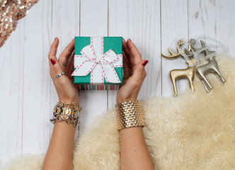 Female hands with gift. Fashion accessories, wrist watches, glamor bracelets