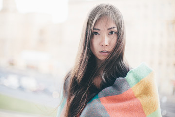 Beautiful woman wrapped in colored blanket looking at camera horizontal