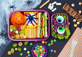 Open Halloween lunch box with sandwich, mandarin, berries and vegetable salad on black background