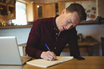 Man writing in diary at home