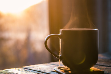 Still life with cup of coffee on the carpathian mountains background during the sunset