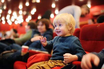 Cute toddler boy watching cartoon movie in the cinema Fotomurales