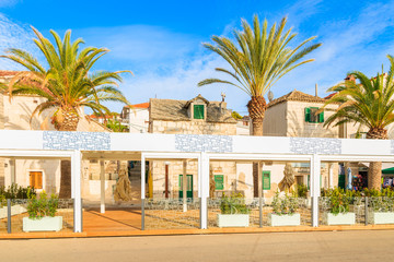 ROGOZNICA TOWN, CROATIA - SEP 5, 2017: Restaurant terrace and typical houses with palm trees in Rogoznica port on sunny summer day, Dalmatia, Croatia.