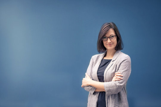Portrait of confident businesswoman with arms crossed. Female leader against blue background. Copy space.
