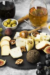 Snacks with wine - various types of cheeses, figs, nuts, honey, grapes on a gray background