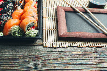 on the table are in the black container, sushi set with photo frame