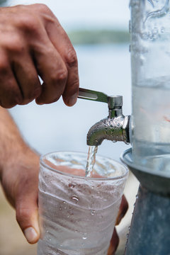 Pouring a drink of ice water from a spout