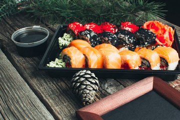 on the table are in the black container, sushi set with photo frame and Christmas attributes