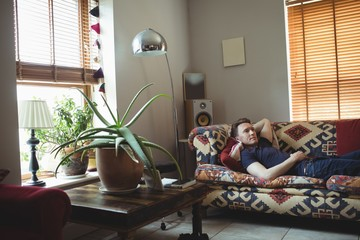 Man relaxing on sofa in living room