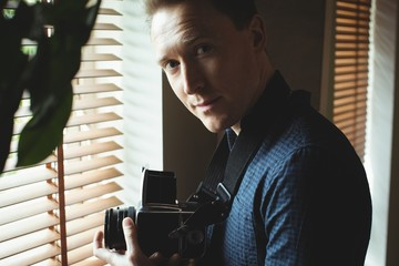 Handsome man holding vintage camera near window