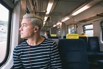 Man listening music while travelling in metro
