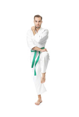 Young man practicing karate on white background