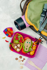 Open Halloween lunch box with school lunch on grey concrete background