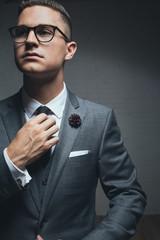 An elegant young man adjusting his tie looking away